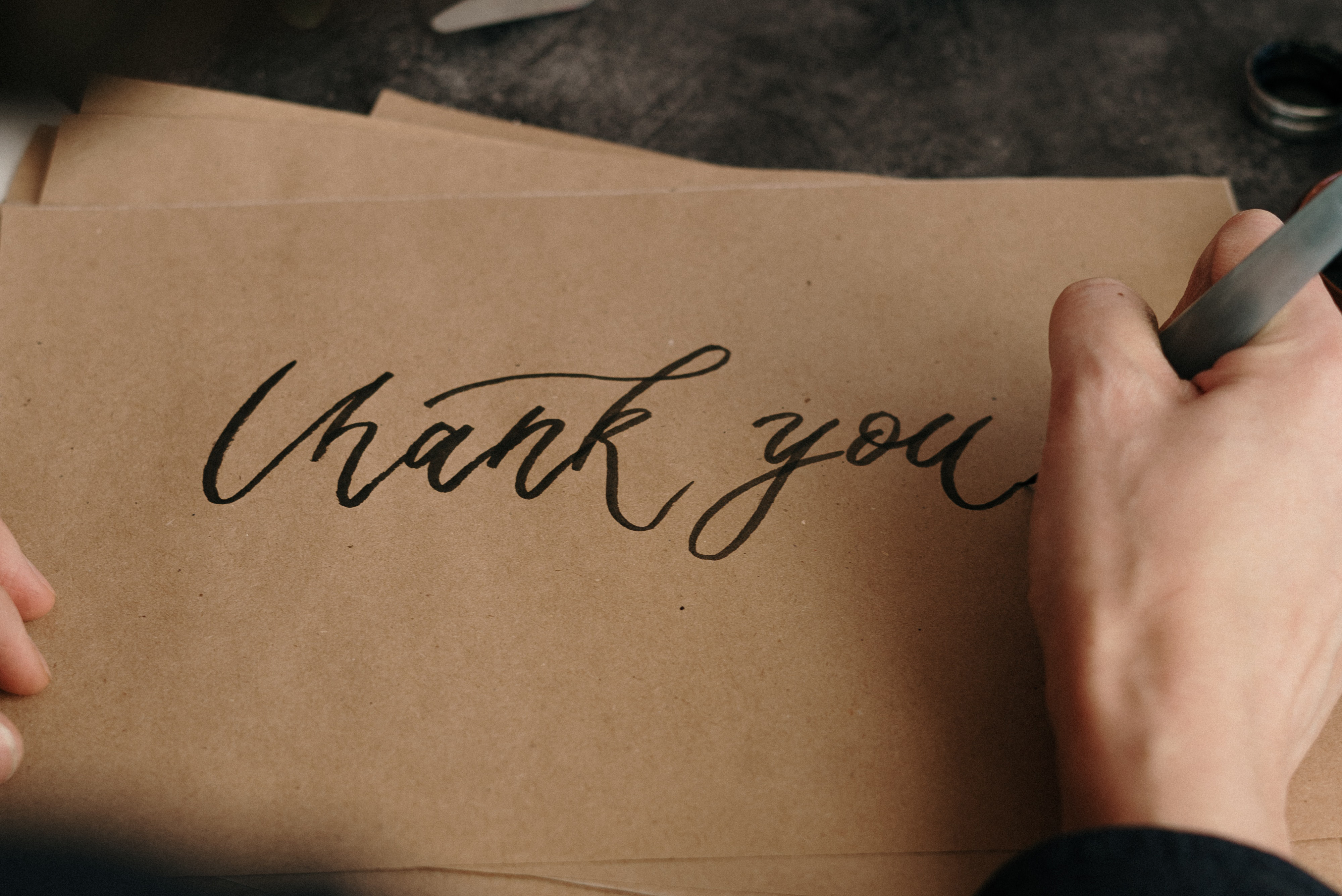 """Close up of a woman's hand writing """"thank you"""""""