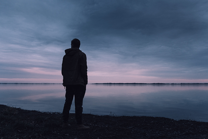 Lone person standing alone on the bank of a lake.
