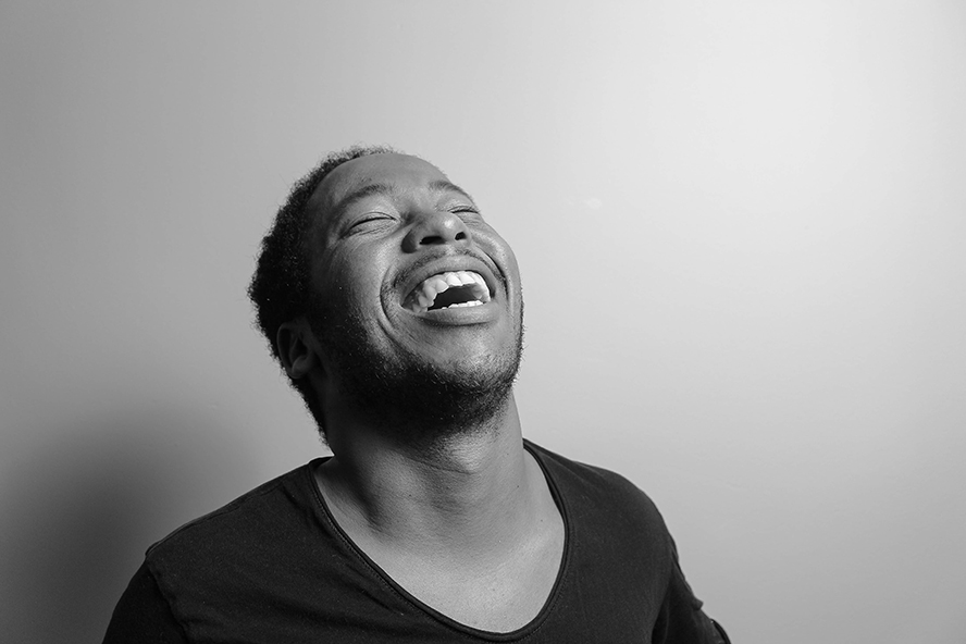 Young guy laughing to himself. Black and white image.