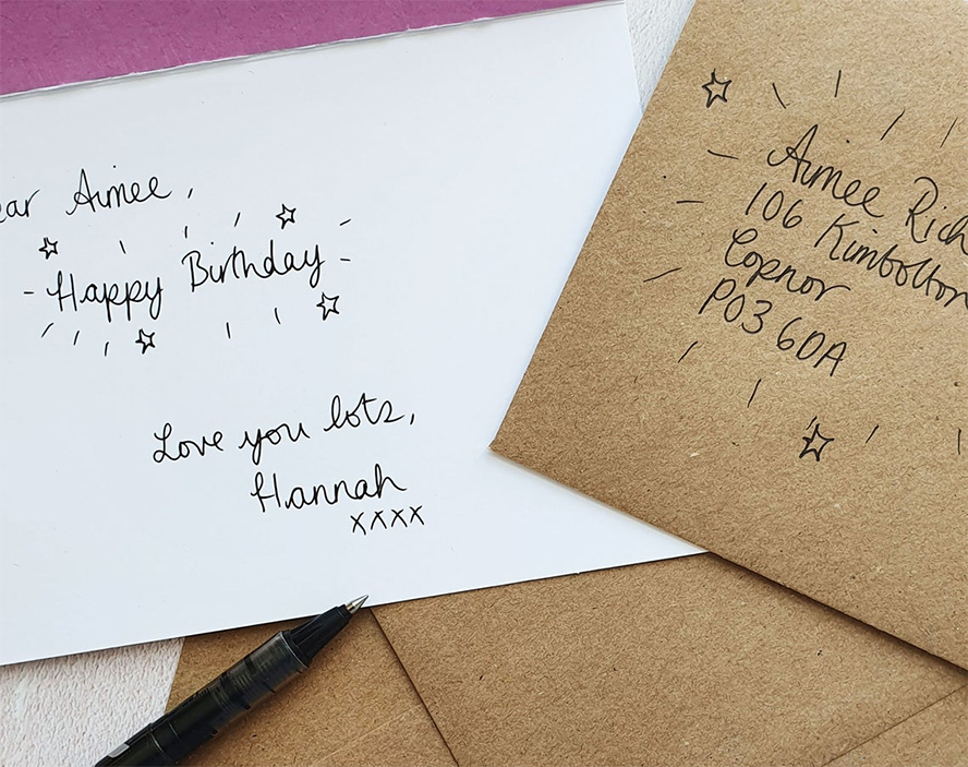 Close up of a handwritten card and envelope.
