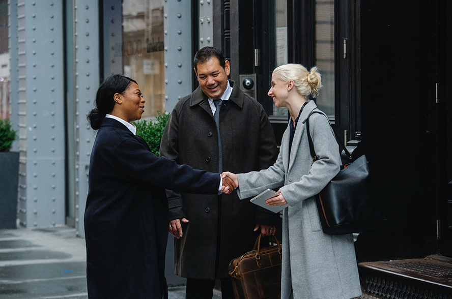 Three businesspeople greeting each other warmly.