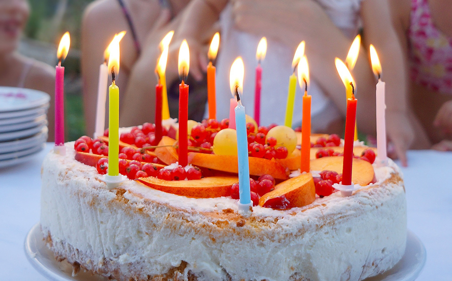 A birthday cake with fruit on top and candles.