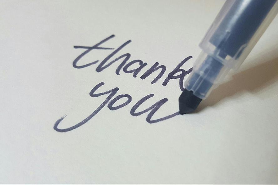 """Close up of a pen written """"thank you""""."""