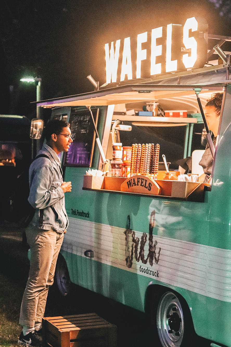 """A customer buying food from a food truck called """"Waffles""""."""