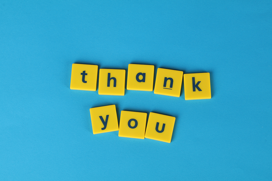"""""""Thank You"""" in yellow tiles on a blue background."""