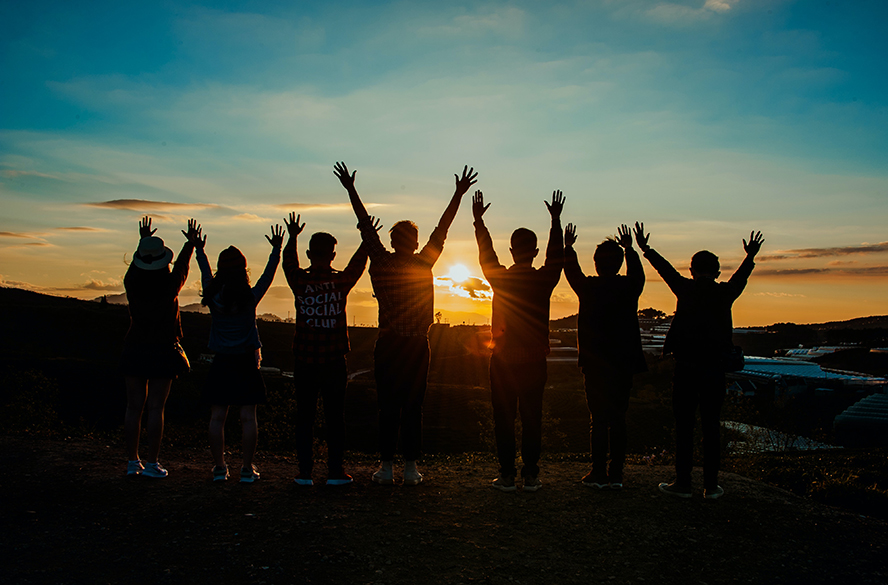 A group of successful people outside at dawn, hands raised to the Sun.