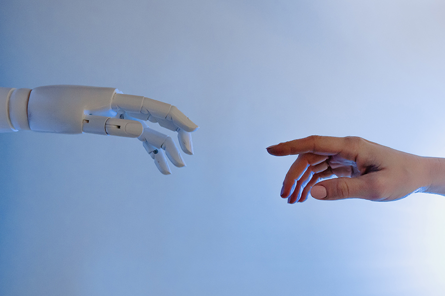 A robot and a human hand reaching for each other.