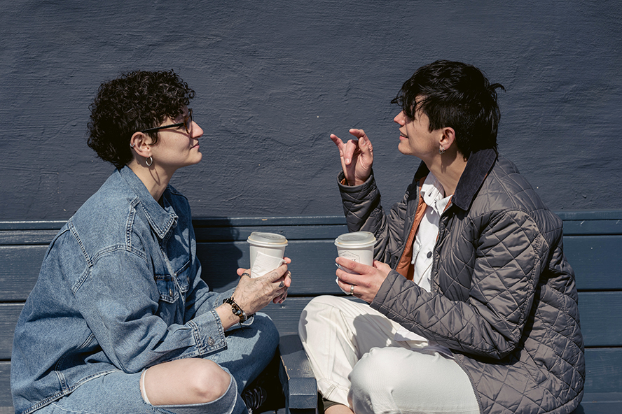 Two women talking to each other over coffee.