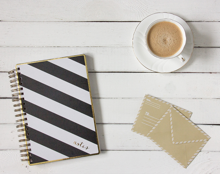 Two envelopes, a notepad, and a cup of coffee