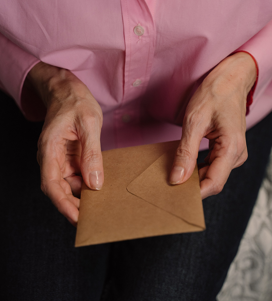 Close up of an envelope being held in a woman's lap.