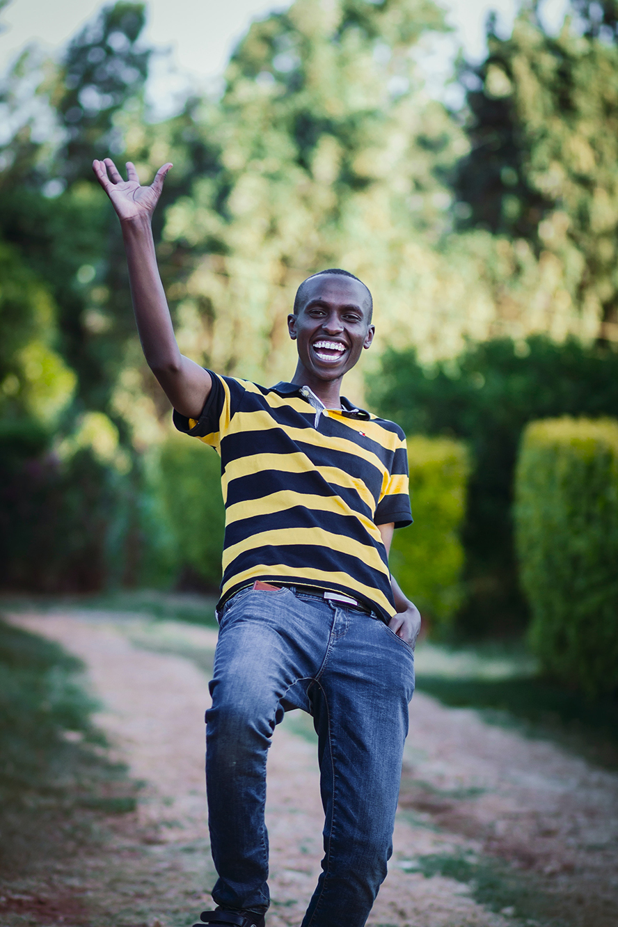 Guy waving big at the camera with an exuberant smile.
