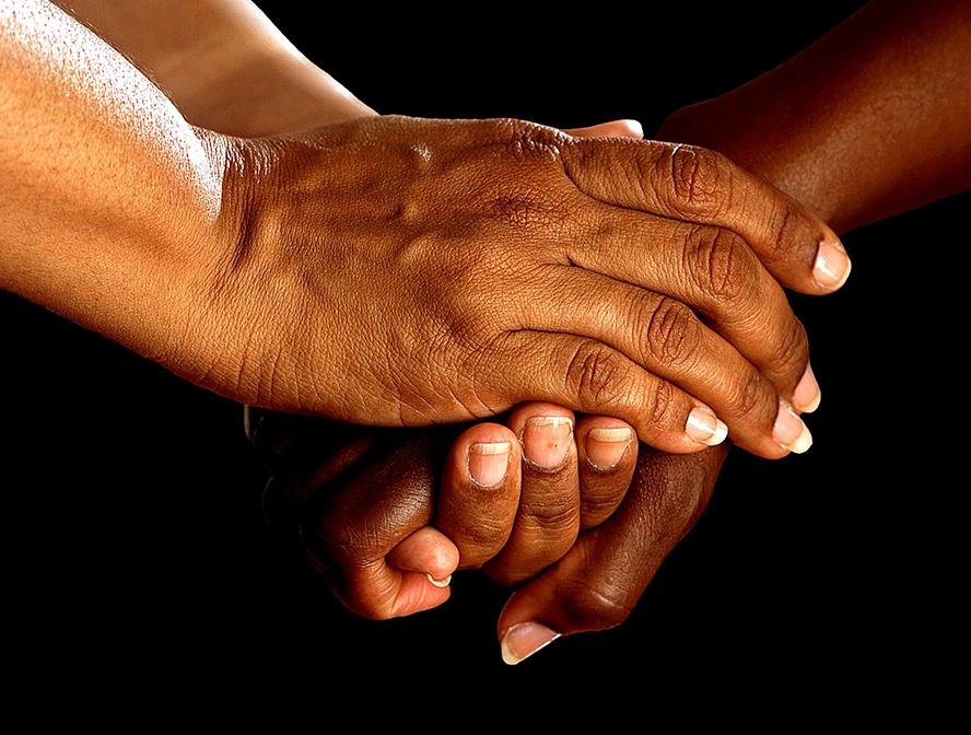 Close up of two people clasping hands in friendly gesture.
