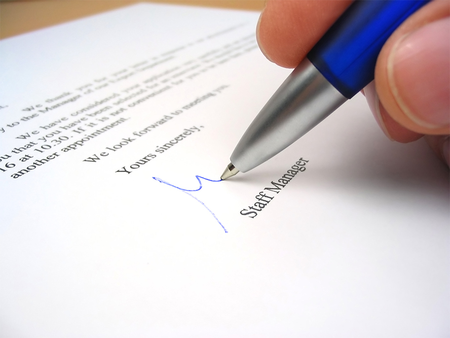 Close up of someone signing a letter.