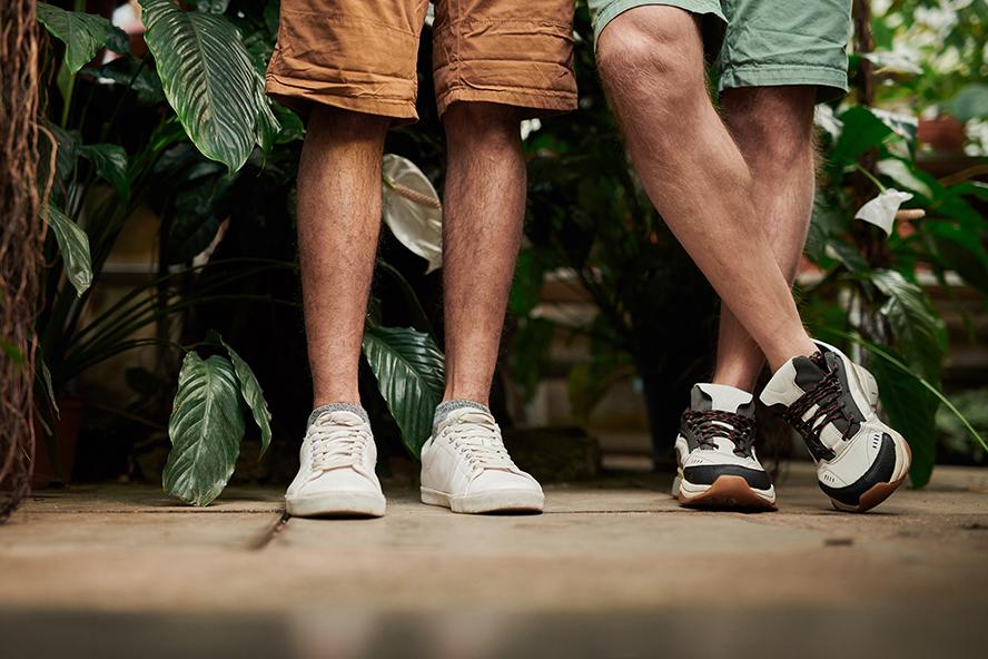 Two men's feet wearing shoes.