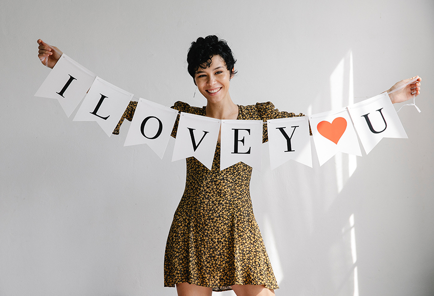 """A woman smiling, holding a banner that reads """"I Love U""""."""