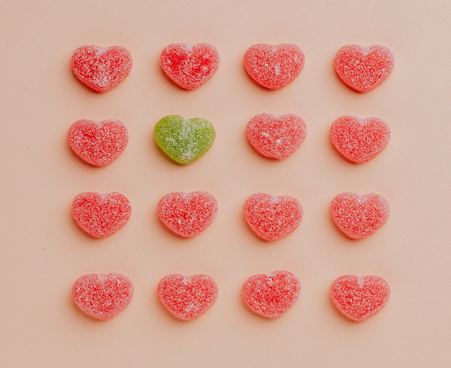 16 candy hearts in a grid pattern. All but one of the hearts are red. The standout is green.