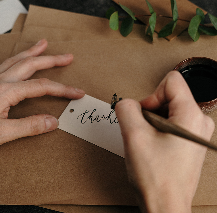 Someone applying a calligraphed thank you on a card