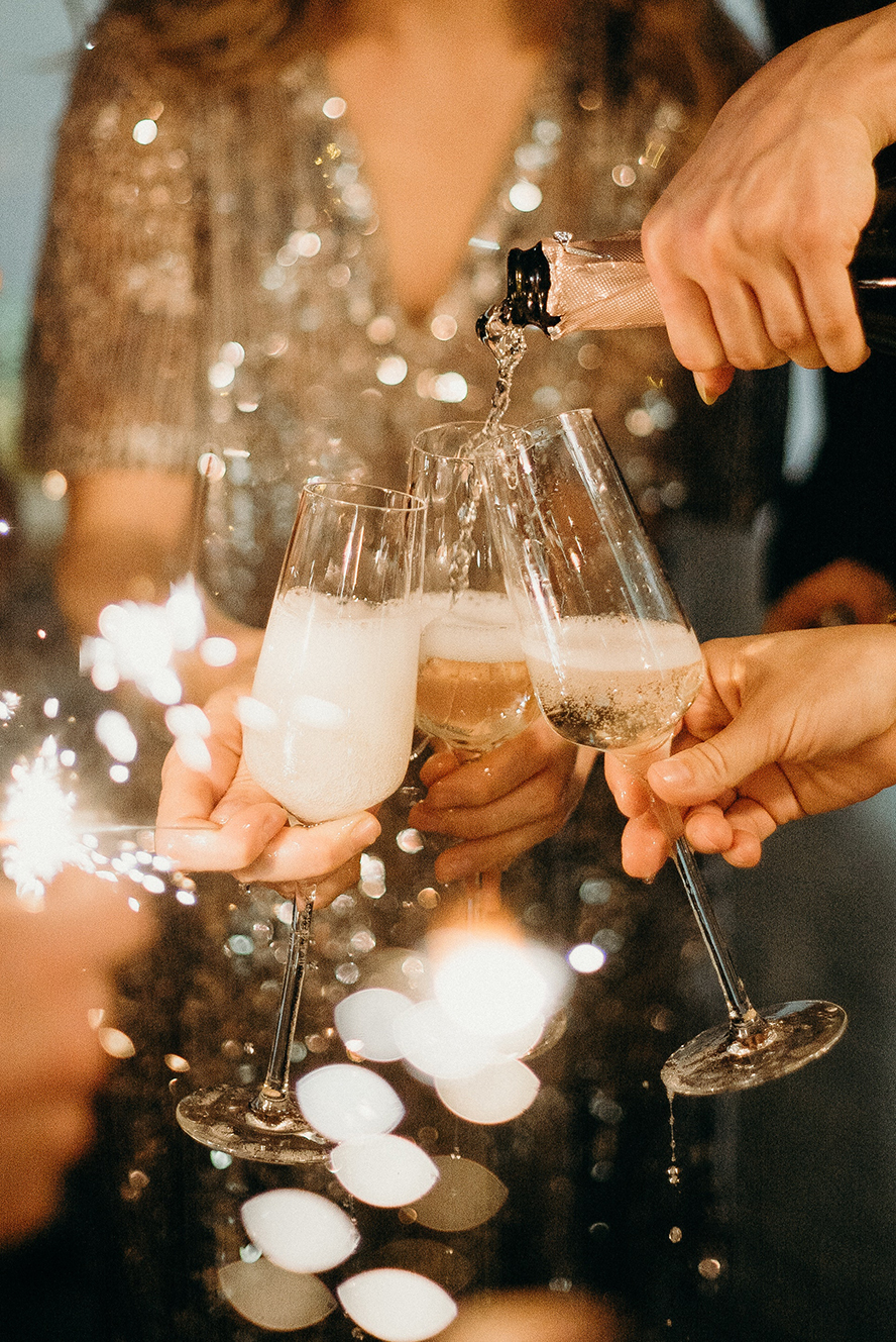 Party guests pouring champagne.