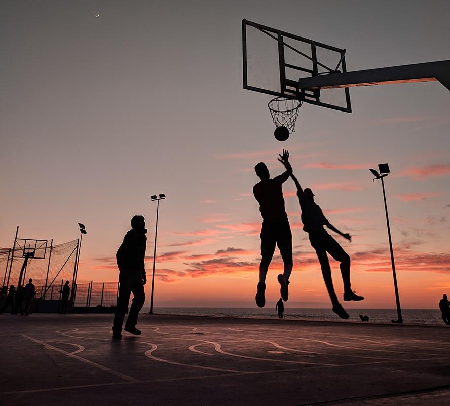 Three guys playing basketball during twilight.
