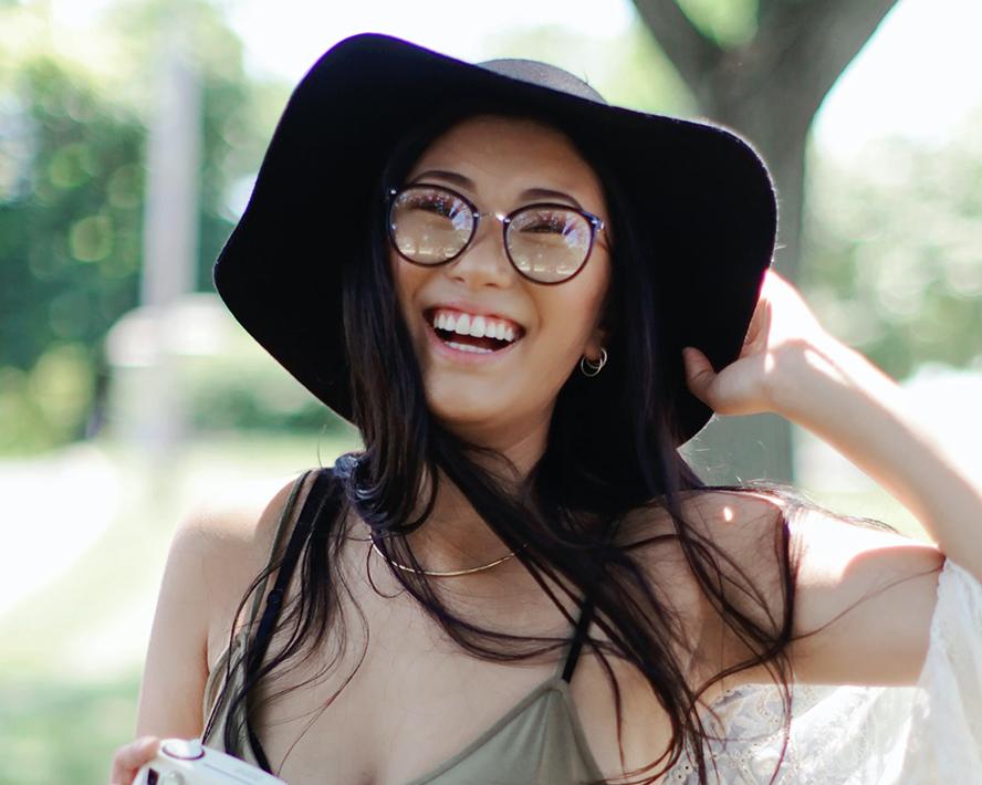 Asian woman smiling at the camera outdoors.