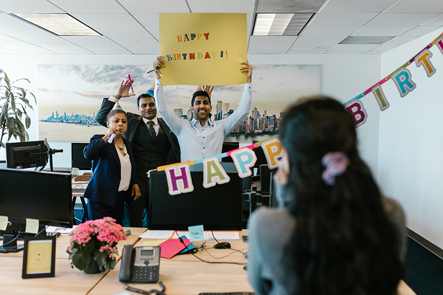 """Coworkers holding a sign that reads """"happy birthday"""". They're suprising their coworker."""