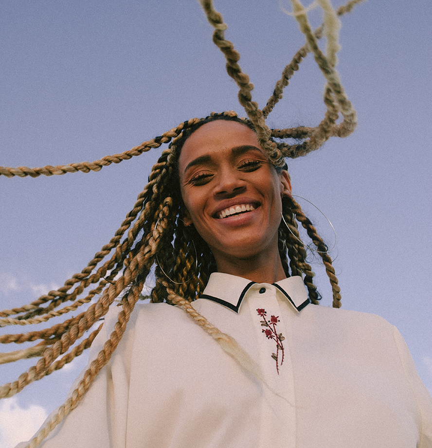Woman smiling close to camera while twirling her braided hair.