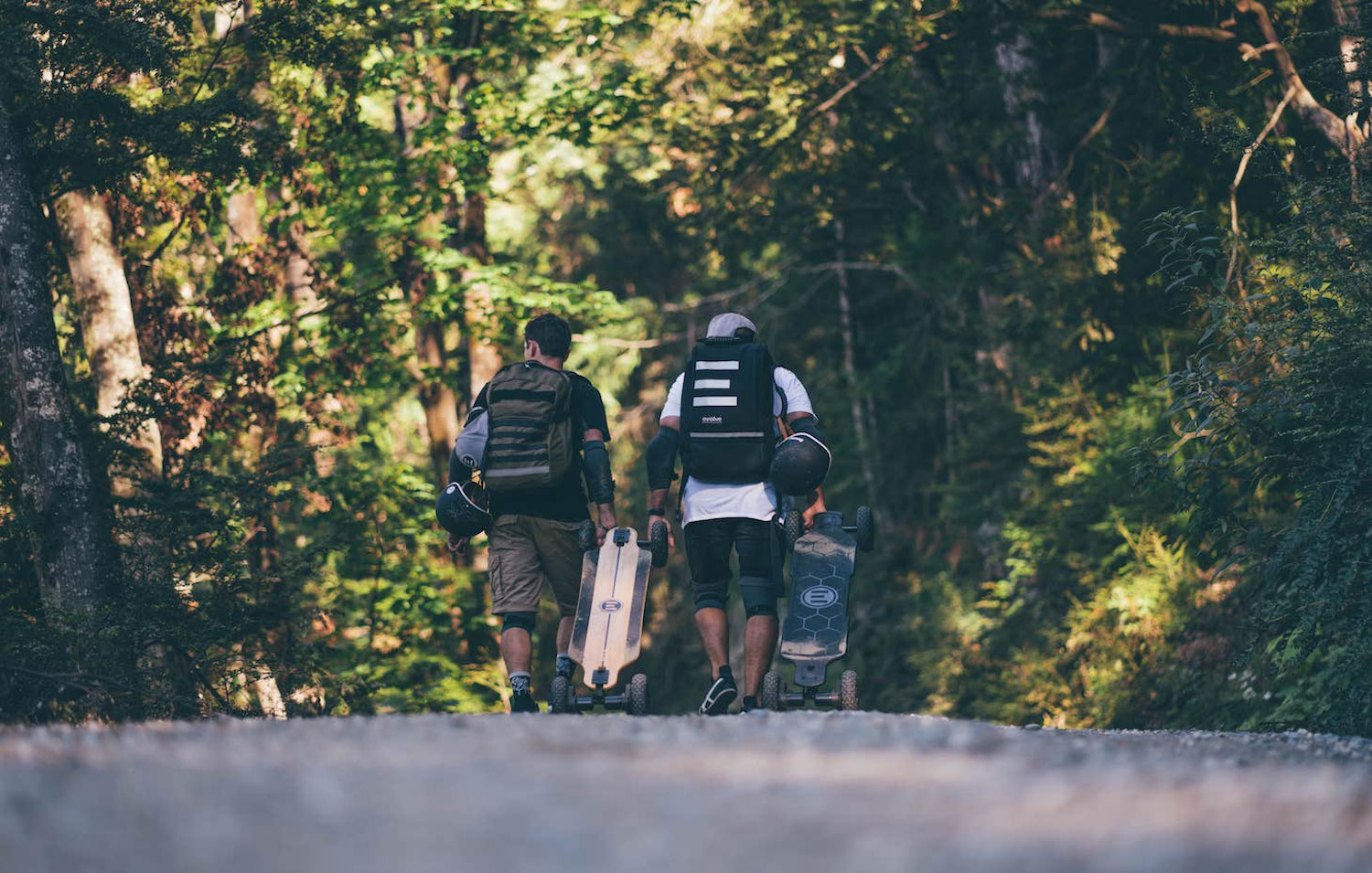 two people walking away with their electric longboards and Thousand helmets