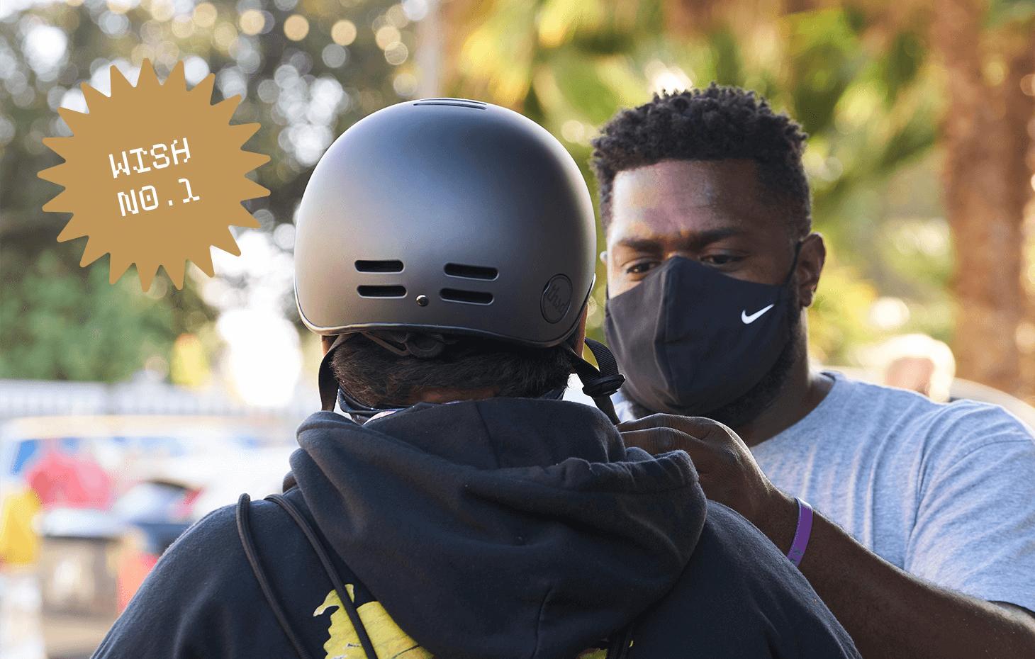 John J. helping someone try on a black bike helmet.