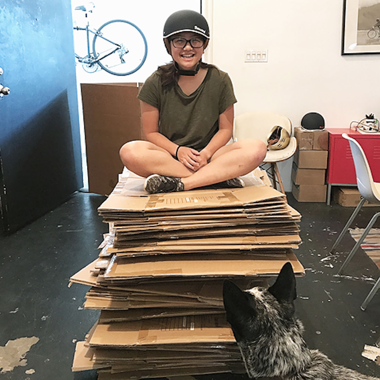 Julia wearing black bike helmet sitting on empty bike helmet boxes