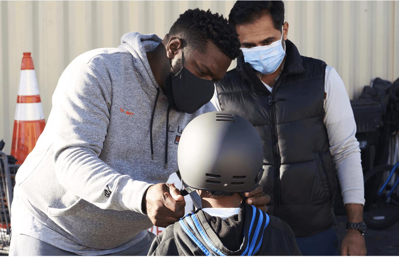 John J. helping someone try on a black bike helmet