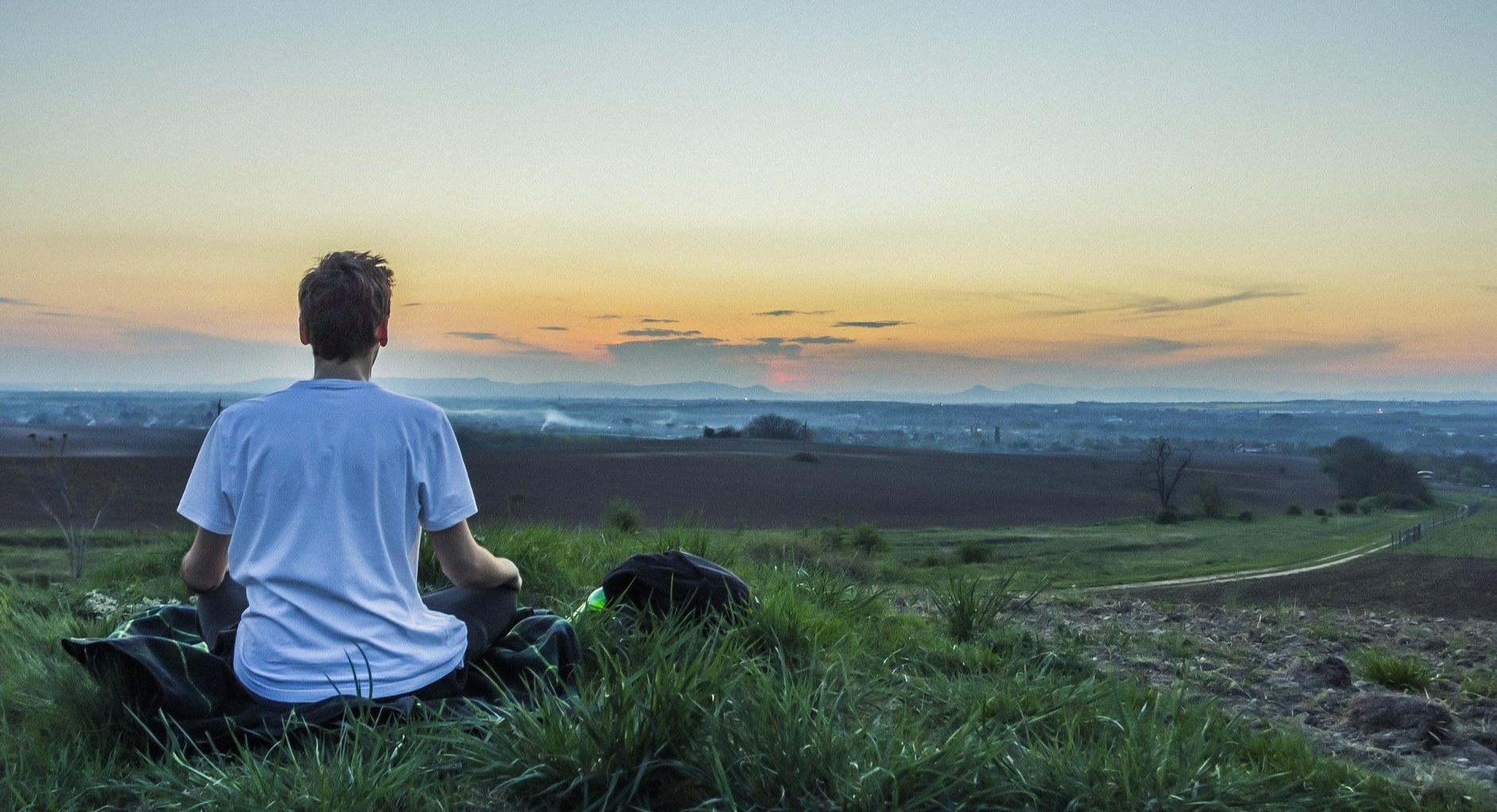man meditating outdoors on hill