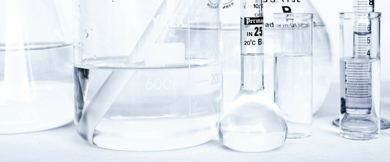 laboratory glassware and vials on white surface