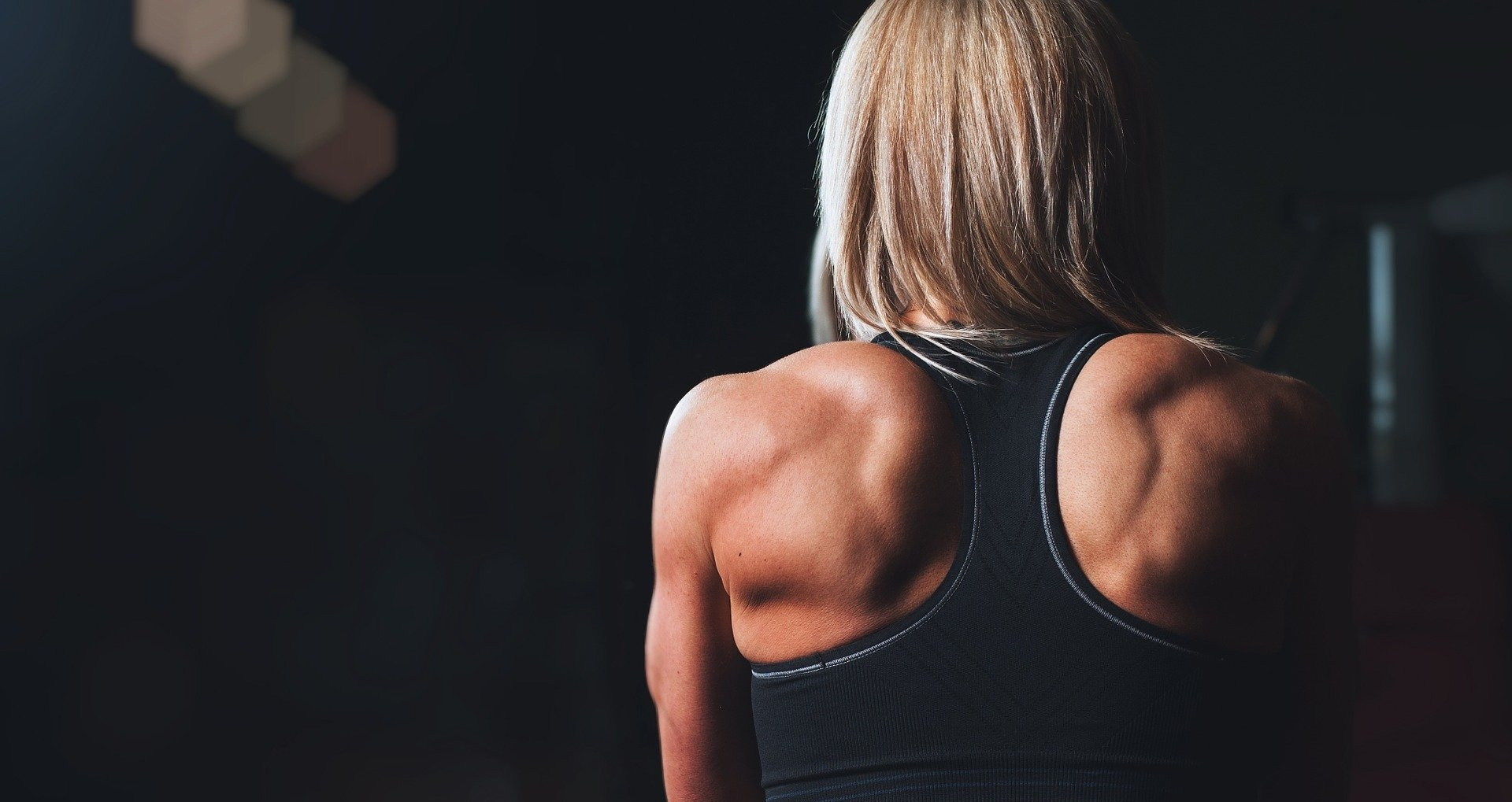 Woman's back whilst working out on dark background