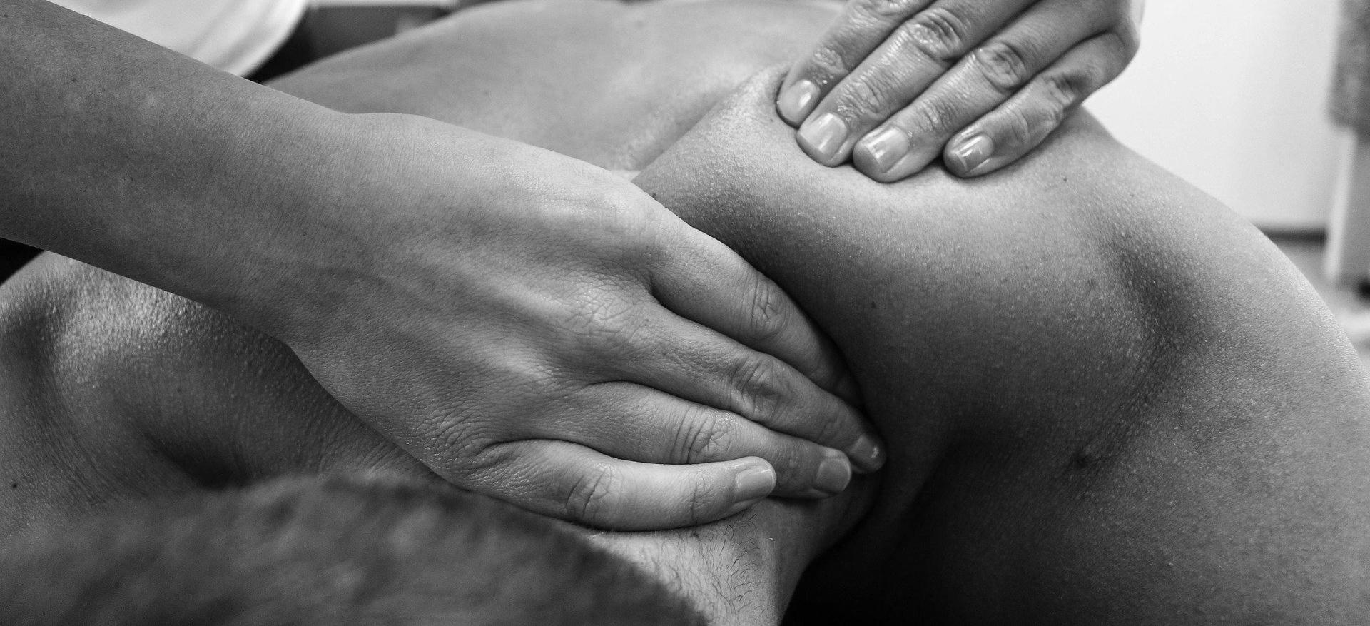 man getting shoulder massage black and white