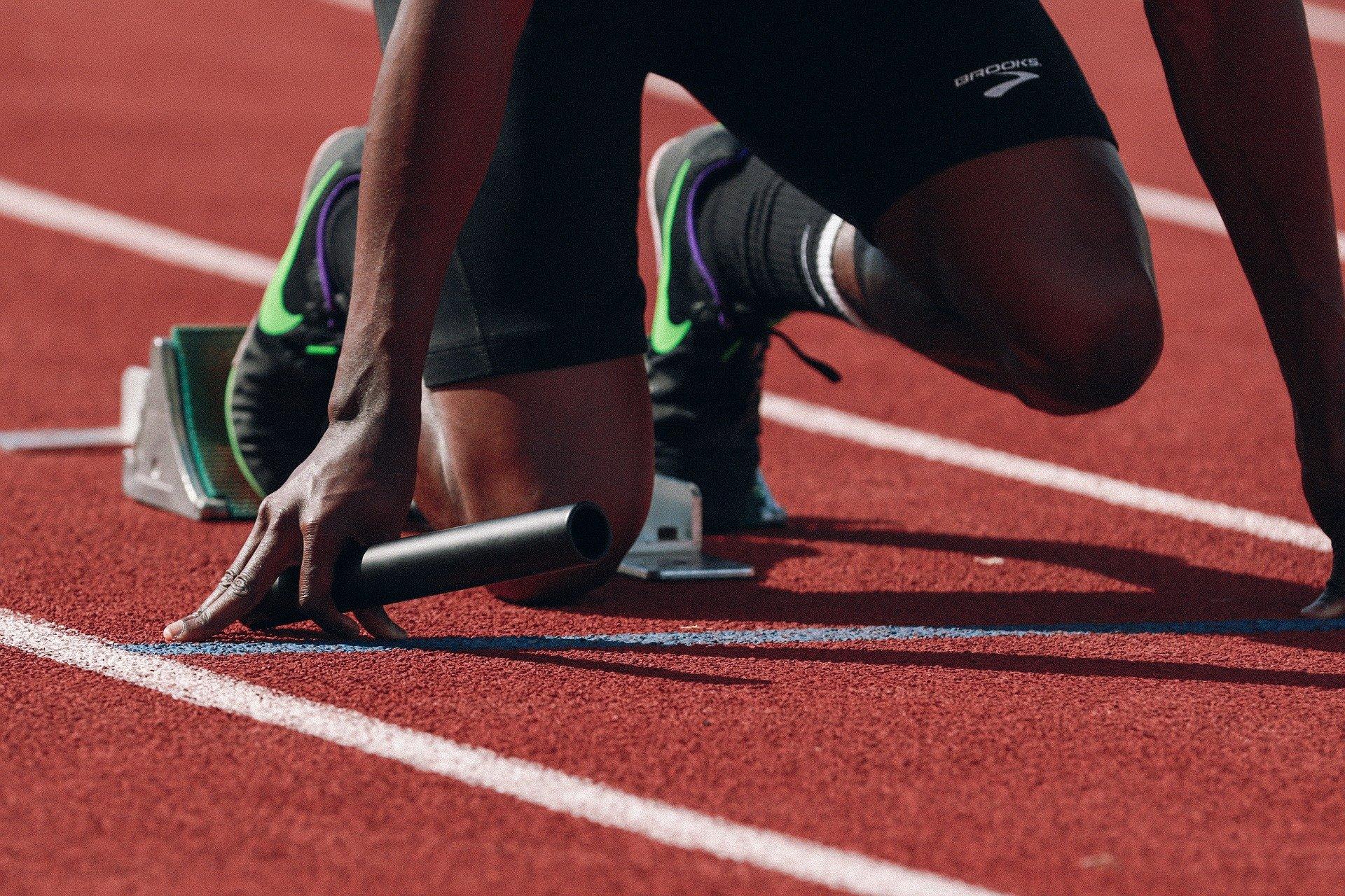 man crouching at start of running track