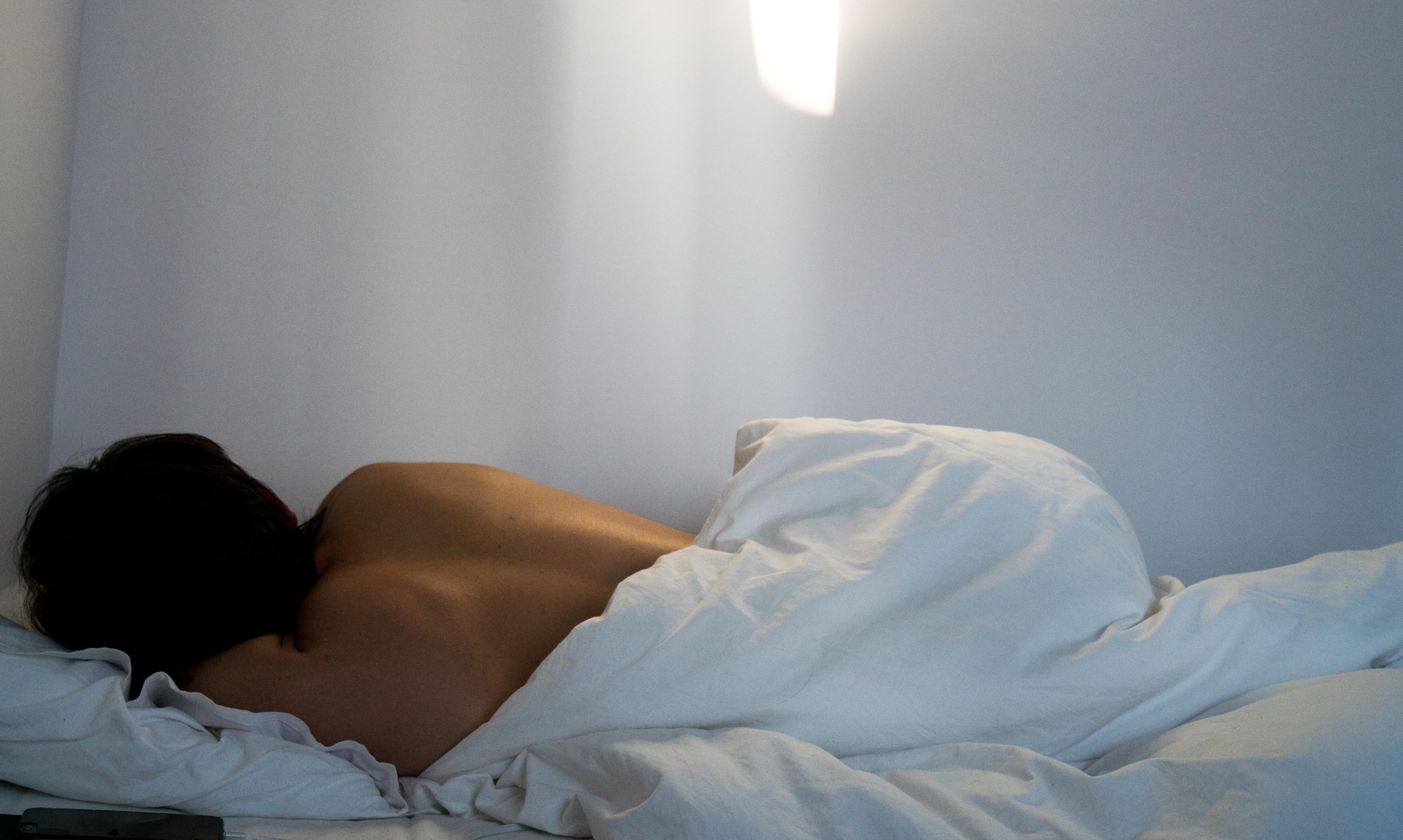 woman sleeping in white bed facing away