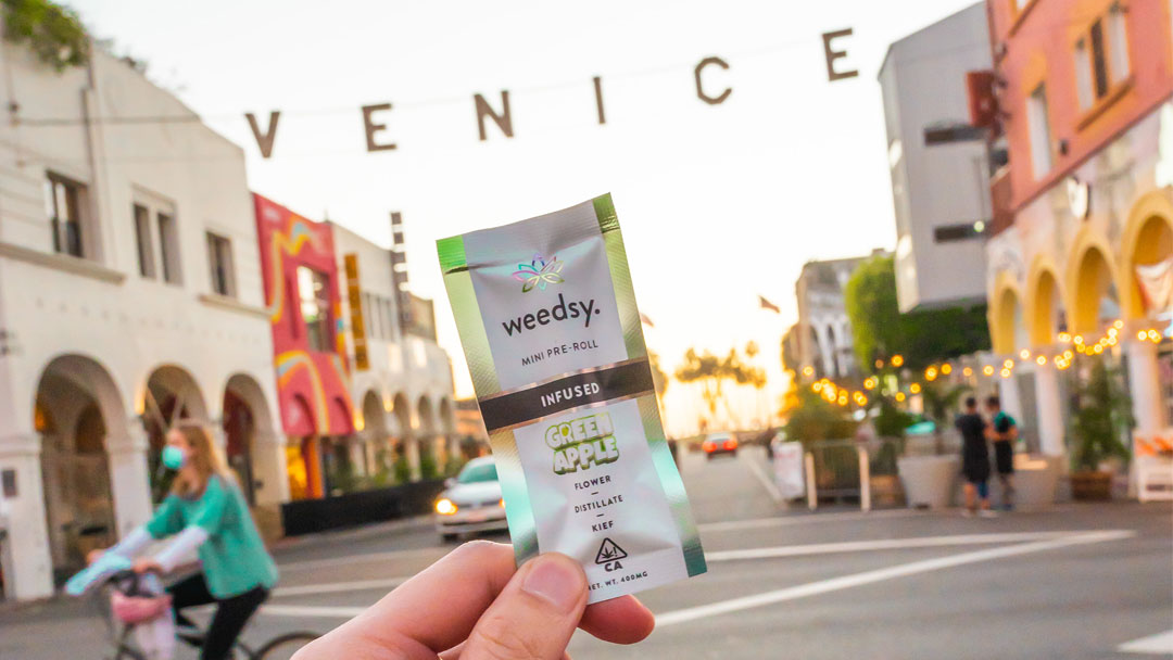 Person holding up a Weedsy pre-roll at Venice Beach